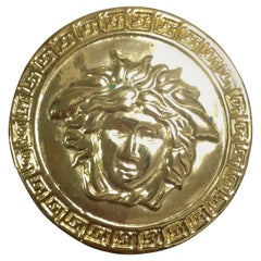 Vintage GIANNI VERSACE classic round pin brooch with its iconic medusa motif.