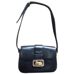 Vintage Celine black leather classic shoulder bag with golden logo closure.