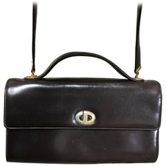 Vintage Christian Dior dark brown leather shoulder bag with CD motif and strap.