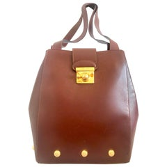 Vintage Salvatore Ferragamo brown shoulder bag with golden motifs and closure.
