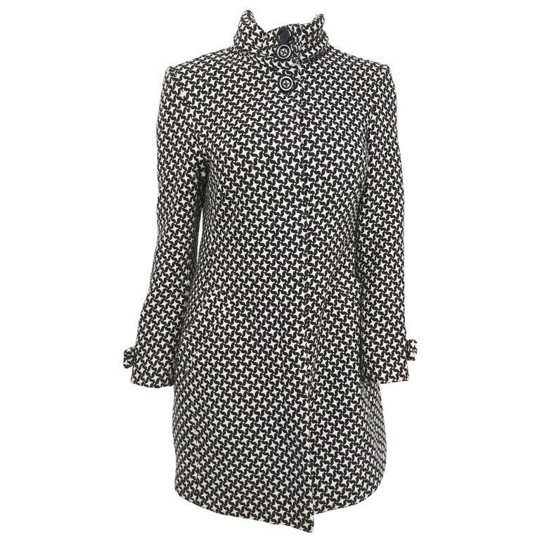 New with original tags black and white hounds tooth Coat, DoubleBreast, Has 4 large black buttons on front of Coat, Two large black buttons on backside of Coat, Also has two front slit pockets, Has lapel collar, % Polyester lining, Great for Fall and Winter wear, Can be worn with dress slacks, Jeans, Skirts, and Leggings.