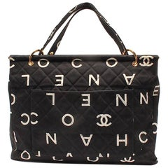 Vintage CHANEL black fabric canvas large tote bag with white Chanel CC prints.