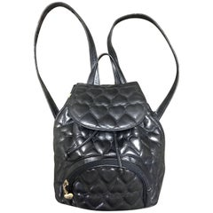Vintage MOSCHINO black heart quilted leather backpack with golden heart motif.