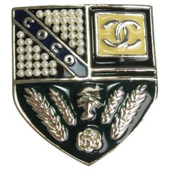 CHANEL Escutcheon Brooch in Pale Gilded Metal, Pearls and Colored Resin