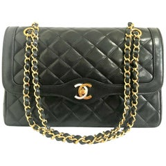 Vintage Chanel black 2.55 classic double flap bag with gold and silver CC motif.
