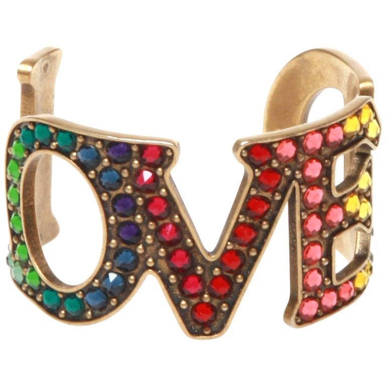 ea6dc104504 Gucci Loved Cuff For Sale. Gold-tone Gucci Loved cuff featuring multicolor  crystal. Includes jewelry pouch and box.