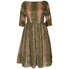 A Vintage 1950s Apricot, Green and Brown print swing cinch party dress