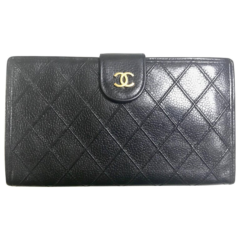Vintage CHANEL black caviar leather wallet with stitches and gold tone CC motif.