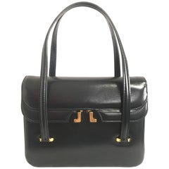 Vintage LANVIN black leather handbag with golden logo motif. Classic purse.