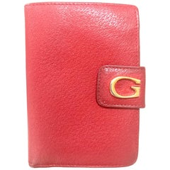Vintage Gucci red pigskin leather wallet with golden G logo hardware closure.