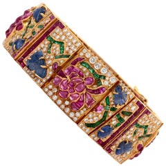 Mutli Gem Yellow Gold Bracelet with Diamonds, and Sapphires in a Flower design.