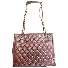 Vintage CHANEL brown quilted lamb leather classic tote bag with golden chains.
