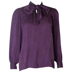 A Vintage 1970s silk purple pussy bow blouse by Yves Saint Laurent