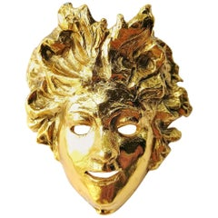 Gilded metal 'mask' brooch, Maison Goossens, 1990s, France.