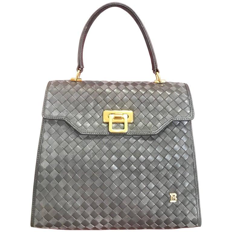 Vintage Bally taupe grey intrecciato leather kelly handbag with gold tone logo.