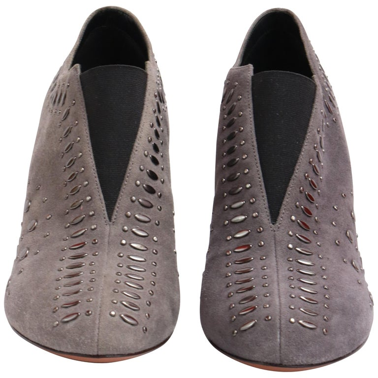 These pair of ALAIA heels are the perfect winter shoes! Made with grey suede and an intricate studded design.  Would look great with any casual daytime look or classy night look.  NBW Comes with original shoebox that has an amazing leather strap and