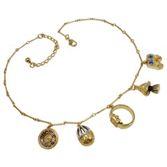 Kenneth Jay Lane Bar Link Charm Necklace in Gold, features Ring, Tree, Roulette