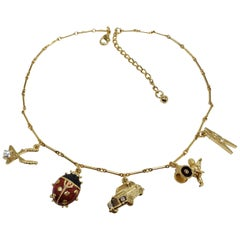 Kenneth Jay Lane Bar Link Charm Necklace in Gold, features Ladybug, Car, Angel