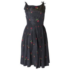 A vintage 1950s black cinch swing dress with embroidered flowers