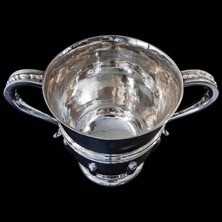 An Edwardian sterling silver two handled cup on a circular foot the plain body having applied strap-work and thread decoration.