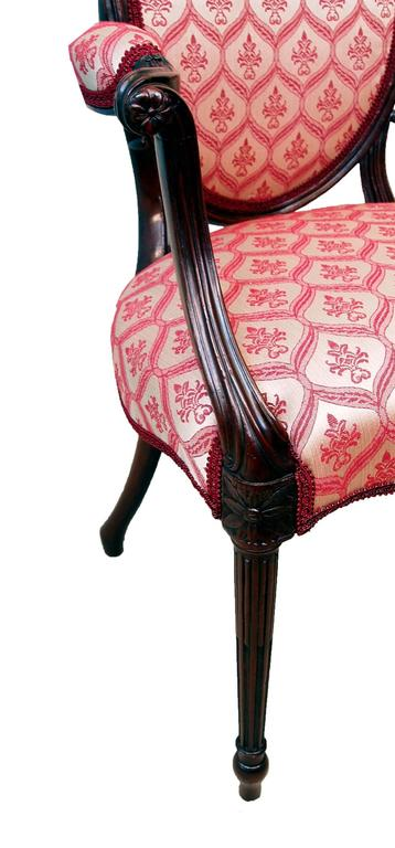 An exceptionally fine late 18th century mahogany armchair having oval back with elegant scrolling arms above shaped seat raised on fine fluted turned tapering legs with exceptional carved decoration throughout.