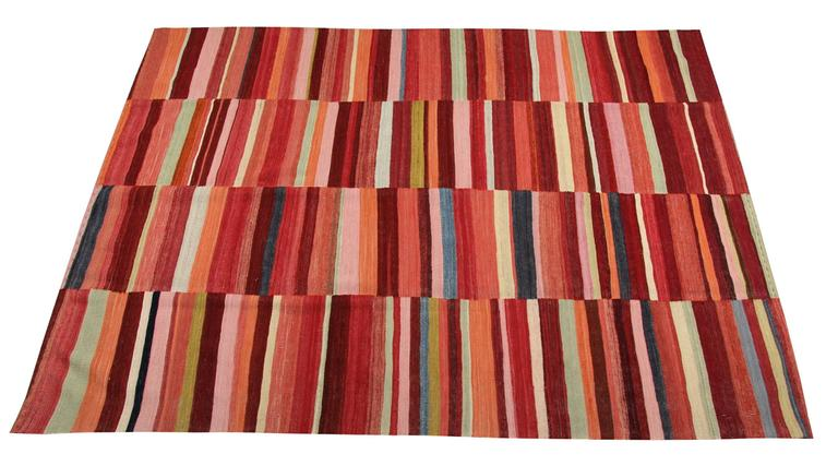 This modern carpet is extremely interesting because of its soft nuances and joyful designs. In fact, the red rug is composed of short stripes which alternate very intense colours: dark red, cherry red, light pink, marron, sand and sea green. The
