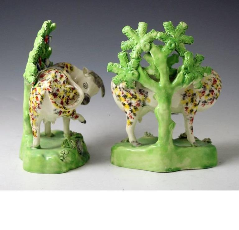 Pair of sponge decorated cows on bases with bocage, pearlware glaze from the
