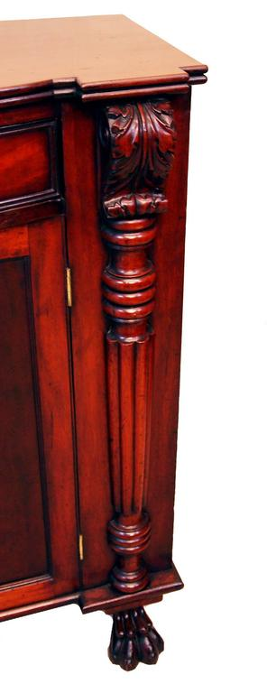 A good quality early 19th century mahogany side cupboard having bowfronted frieze drawer retaining original turned wooden knobs above well figured panelled cupboard doors flanked by very well carved scrolling pilasters and elegant half turned reeded