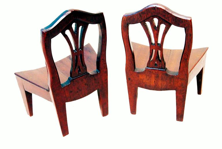 A very rare pair of 18th century mahogany miniature chairs having pierced splat backs and unusual bowed seats raised on square tapered legs.