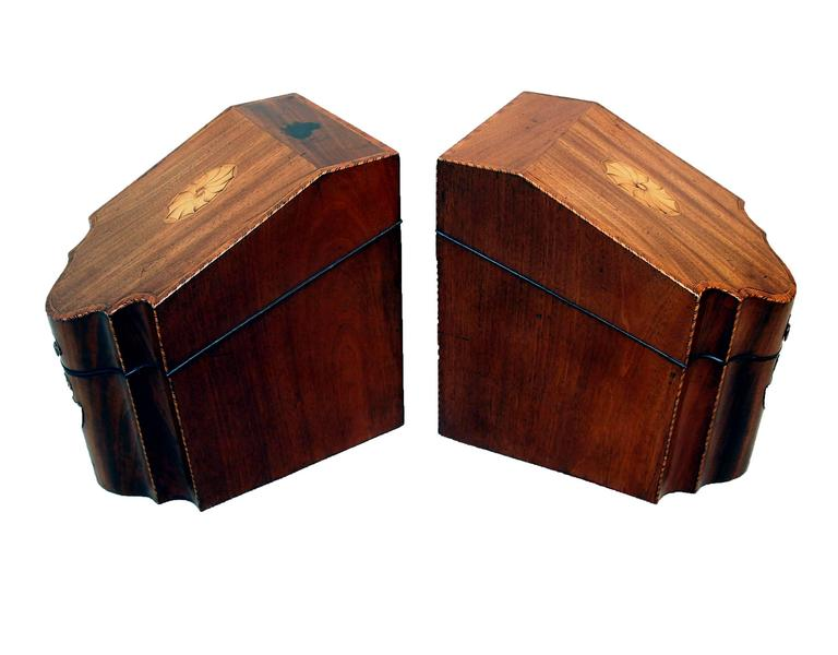 A delightful pair of George III period mahogany knife boxes having  well figured,inlaid and cross banded lift up lids revealing lined interiors.