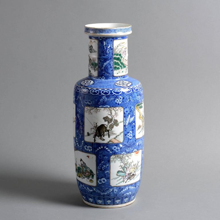 A 19th century famille verte porcelain rouleau vase, decorated throughout with figurative panels on an intricate blue ground.  Qing Dynasty, Xianfeng Period.  Condition: Good, with rim chip restored.