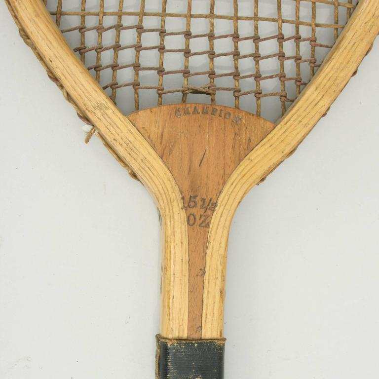 Antique lawn tennis racket.  A wonderful 19th century ash framed lawn tennis racket, 'Champion' with original thick gut stringing (some damage) and trebling on top and bottom. The cedar wood handle, with thin grooves and a black leather collar with