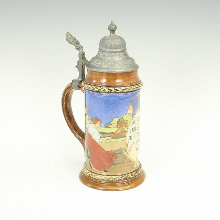 A beautiful German stoneware 1/2 liter beer stein with its original hinged pewter lid. The stein is decorated with a tennis scene and the front is inscribed 'Bei Spiel, und Scherz, Bleibt Froh, Das, Herz', the base with impressed factory mark and