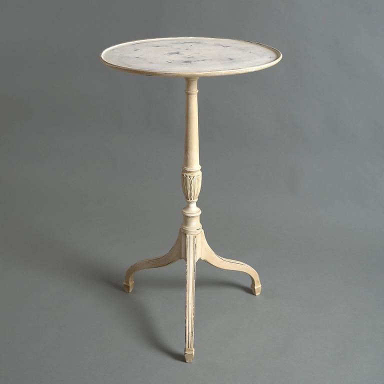 An early 20th century carved and painted occasional table with dish top, set upon a turned stem with carved palmettes and terminating in square tripod legs with spade feet.