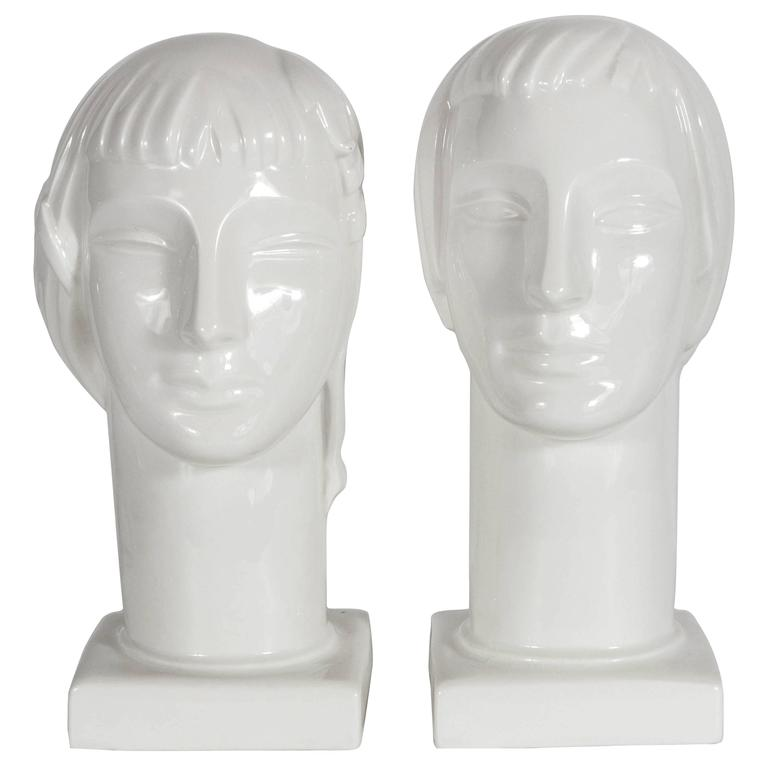 A truly gorgeous duo of male and female Art Deco figural heads sculptured by Geza De Vegh for Lamberton Scammell China Company. A glazed finish give this elegant pair of art pieces an elegant demeanor and serene facial expression. Both pieces are