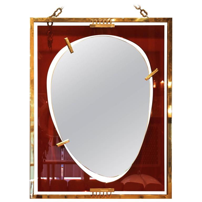 Wall mirror, Gold-plated brass and orange glass, Circa 2010, Italy.