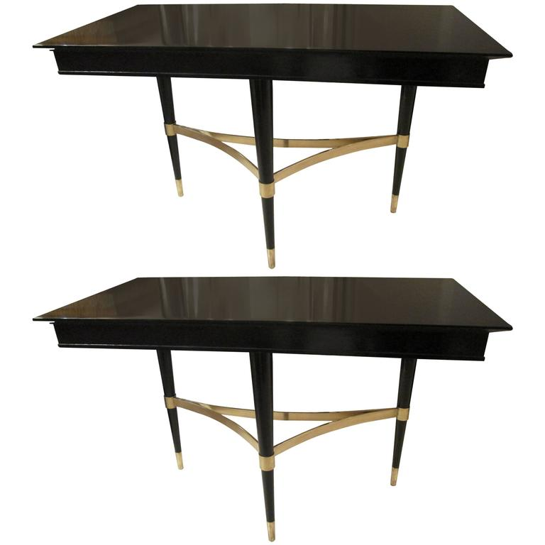 A pair of sculptural ebonized consoles on tripod base with bronze stretchers.