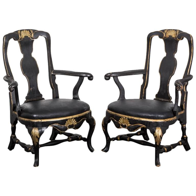 Armchairs Swedish Rococo 18th century period, Sweden. A pair of assembled Rococo armchairs. One made during the Rococo period, circa 1750 and the other made during the 1800s in Sweden. Black painted base with gilded carvings. Both chairs are