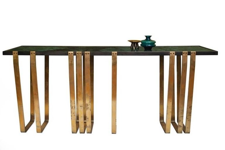 This beautiful contemporary long console is the first piece of the first furniture collection by harryclark and handcrafted in Berlin.  The green marble top is framed in burnished steel and supported by nine elegantly shaped solid brass legs. The