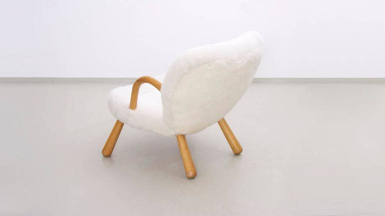 "Rare lounge chair named ""The Clam Chair"" designed by Danish architect Philip Arctander with arms and legs in beech and upholstered in sheep wool and leather buttons."