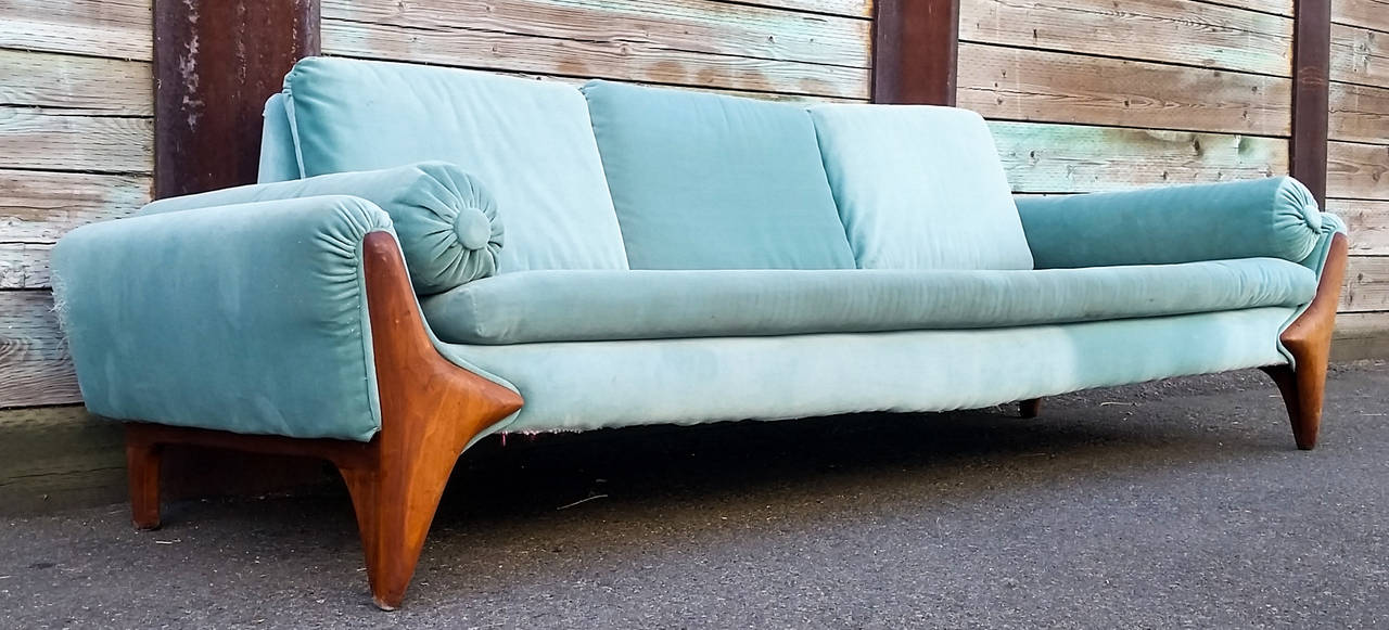 A stunning example of Mid-Century Modern design, this long gondola sofa was designed by Adrian Pearsall for Craft Associates. The sofa is currently upholstered in turquoise velvet that is very weathered and will require reupholstery.