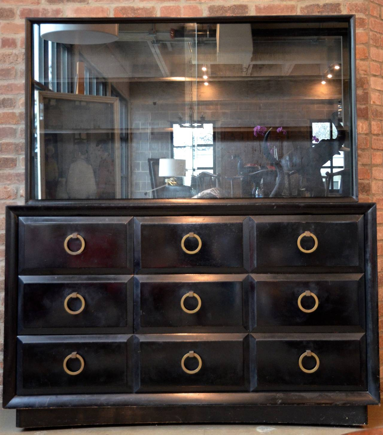 This is one of the most collectible case pieces by T. H. Robsjohn-Gibbings with its iconic brass ring hardware. Dresser has five drawers in base and two adjustable shelves behind sliding glass doors above. Removal of shelves and glass reveal a 27