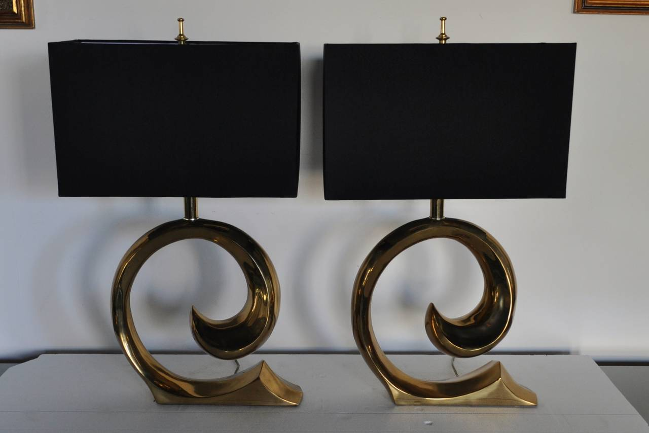 Sculptural pair of brass table lamps by Erwin Lambeth. Modern design features an abstract form base often attributed to Pierre Cardin. Harps and finials included. Lamp shades not included.