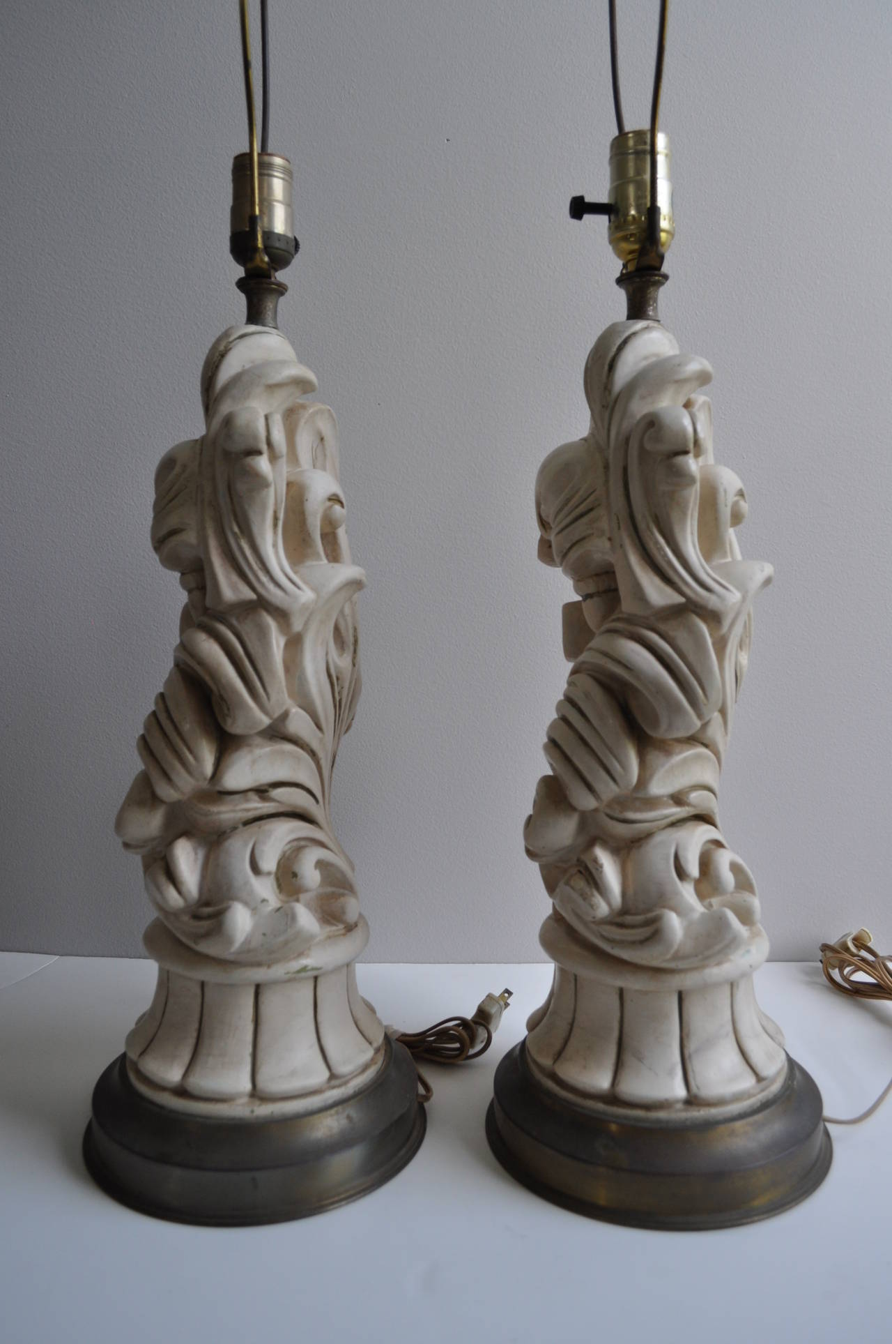 Beautiful pair of sculptural scroll plaster lamps with Baroque styling attributed to Chapman. Features original cream finish and amazing carved scrolled leaf detailing. Plaster bodies attached to brass bases with aged patina. Original 1950s wiring