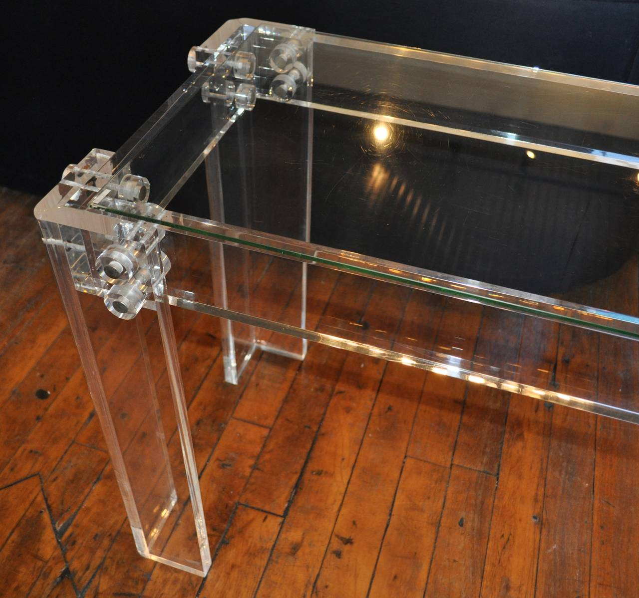 Sculptural Mid-Century Modern Lucite console or sofa table with center rod stretcher and bolted trim details. Thick Lucite frame supports removable glass top. In the style of Charles Hollis Jones and Karl Springer.