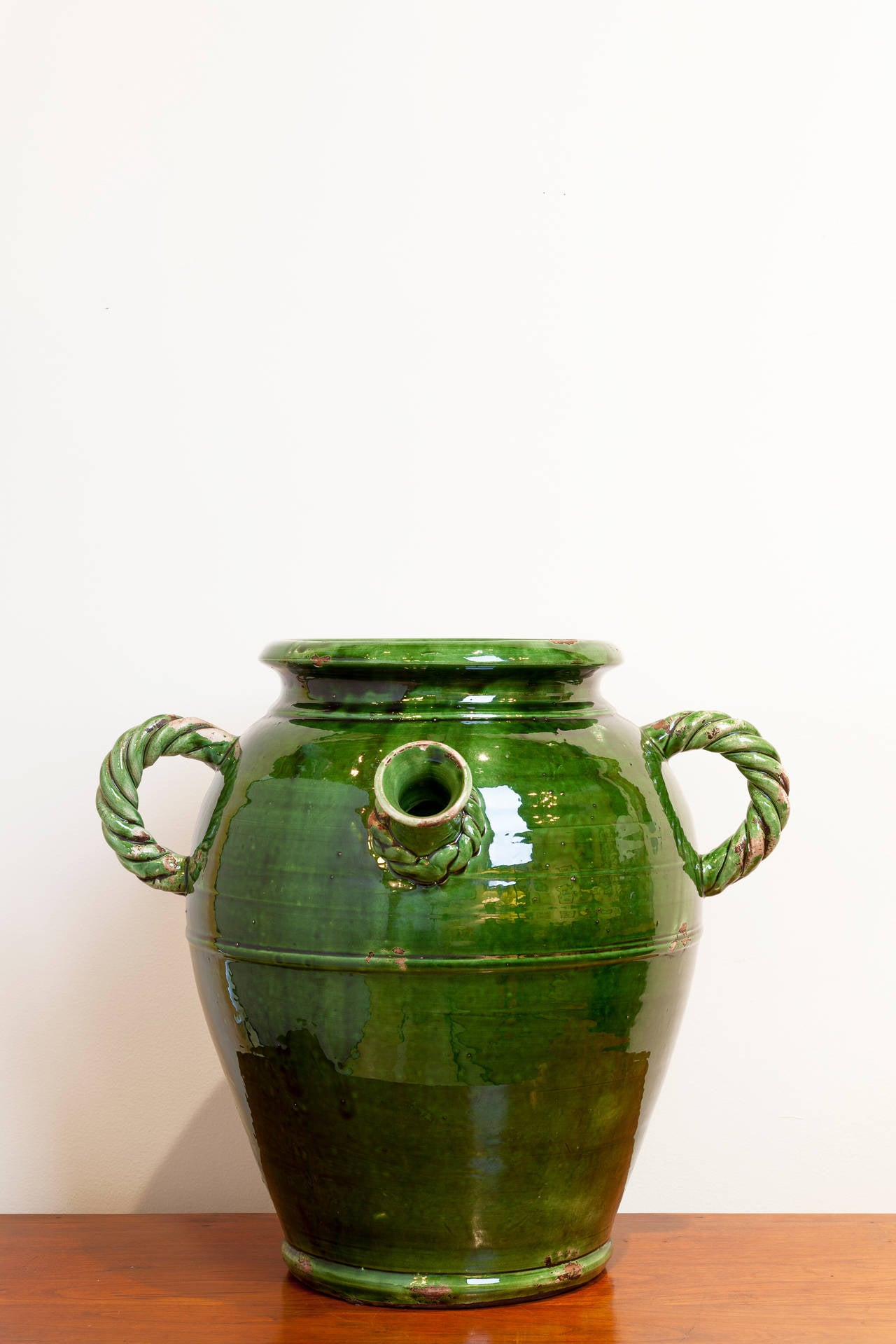 Large French Provençal storage jar, late 19th century. Beautiful deep green glaze with rope-twist handles and detail on spout.