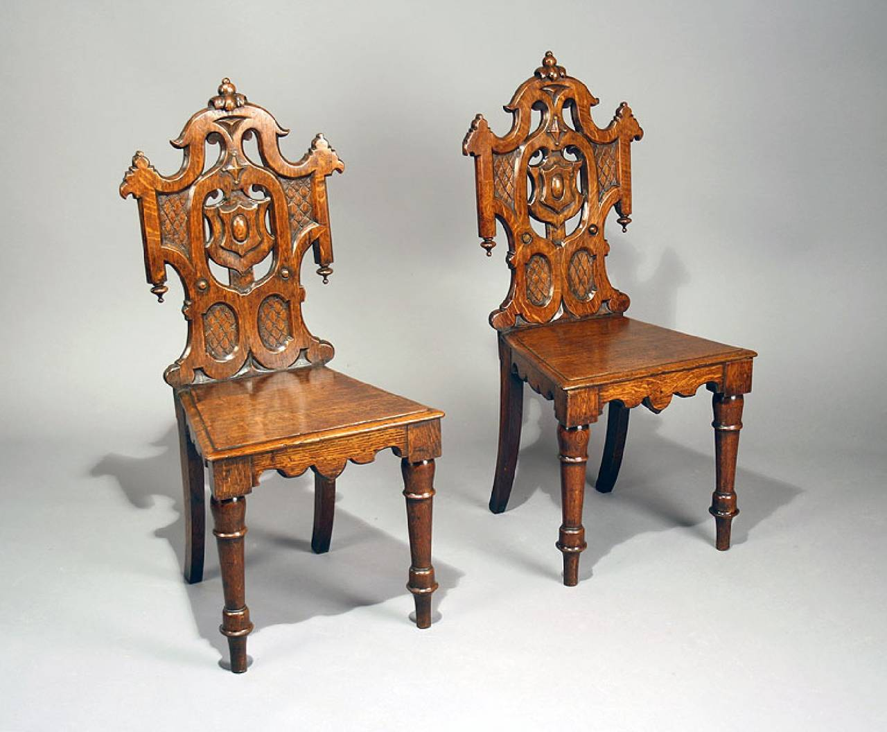 A fine quality pair of antique Gothic oak hall chairs. This pair of hall  chairs - Pair Of Antique Gothic Oak Hall Chairs At 1stdibs