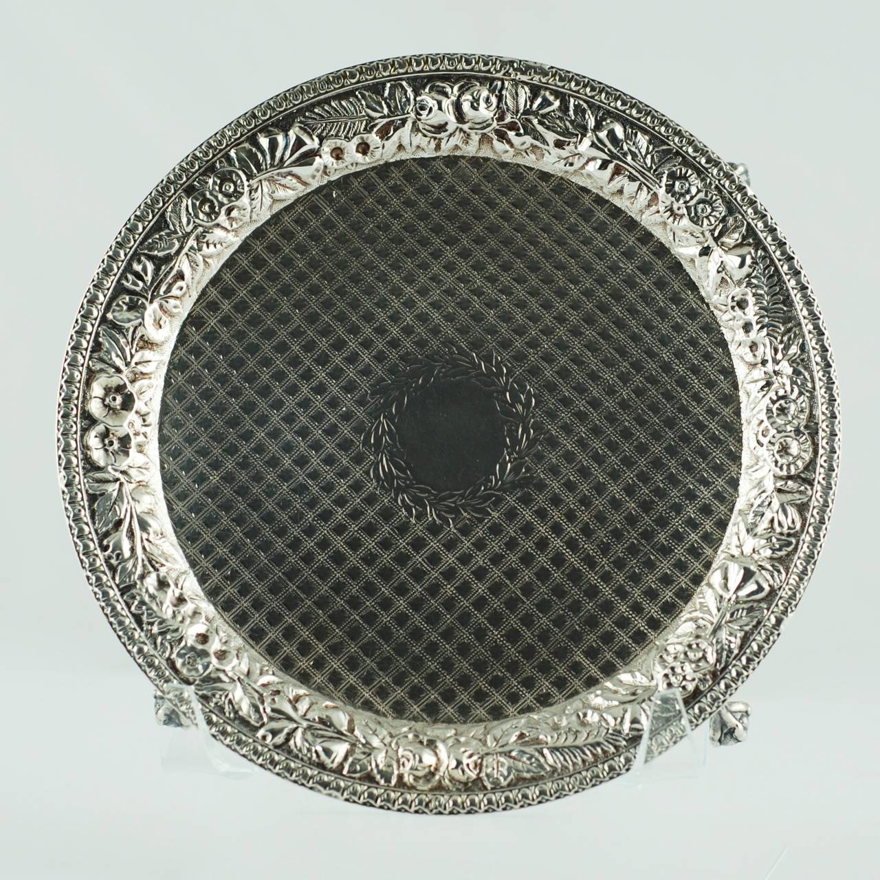 This elegant late 19th century silver salver was made by Baltimore, Maryland based silver manufacturer, S. Kirk & Son. The piece features an ornate chased floral shoulder finished with a banded rim. The face of the tray is decorated with an