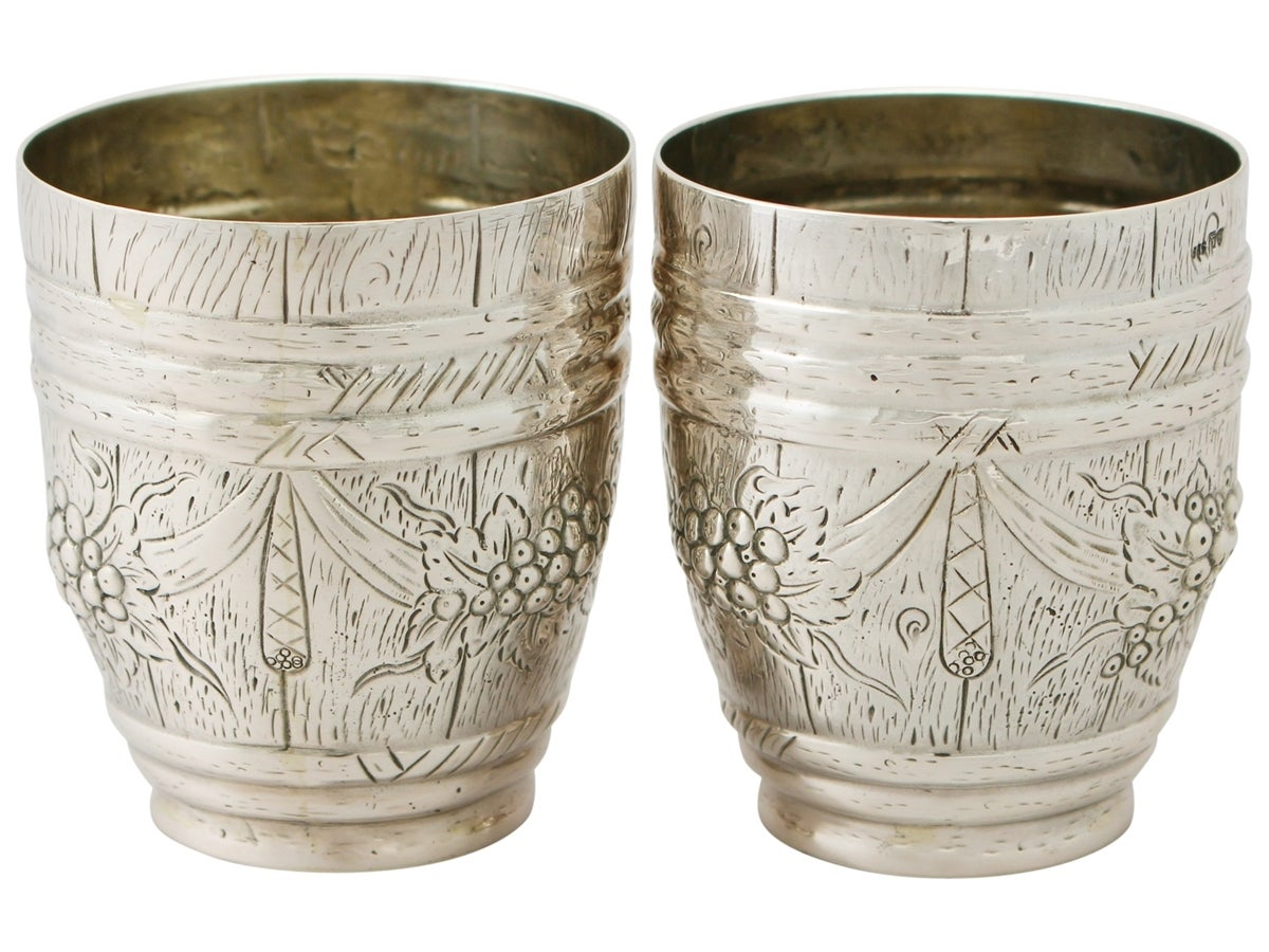 A very good pair of antique German silver beakers; part of our continental silverware collection  These antique German silver beakers have a barrel shaped form.  The surface of each beaker is encompassed with embossed and chased leaf and berry swag