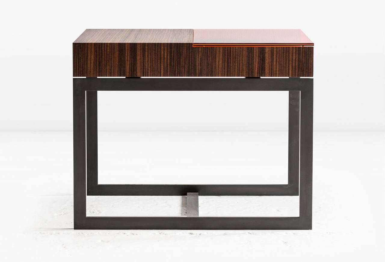The Booker features a frame of Bronze married to wood veneers, creating integrated storage. Glass options in various hues filter and enhance the bronze interior. Shown in premium quartered Santos veneer with Dark Amber glass on a Blackened Steel